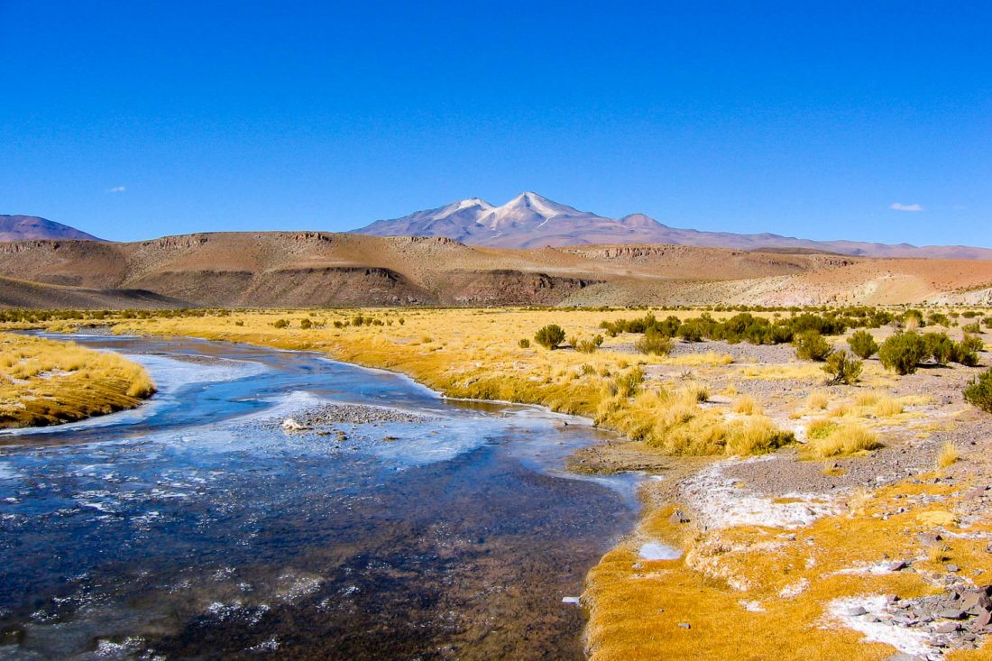 A Landscape Photograph Of The Bolivian Altiplano, Showing A Frozen River In The Foreground And Mountains In The Background.