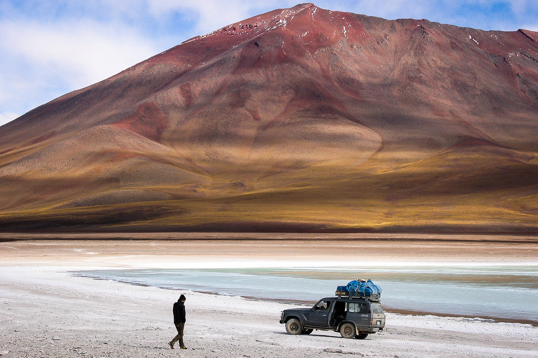 A Landscape Photograph Showing A Man Walking Towards A Toyota 4x4 In The Bolivian Altiplano With An Orange And Red Mountain In The Background.