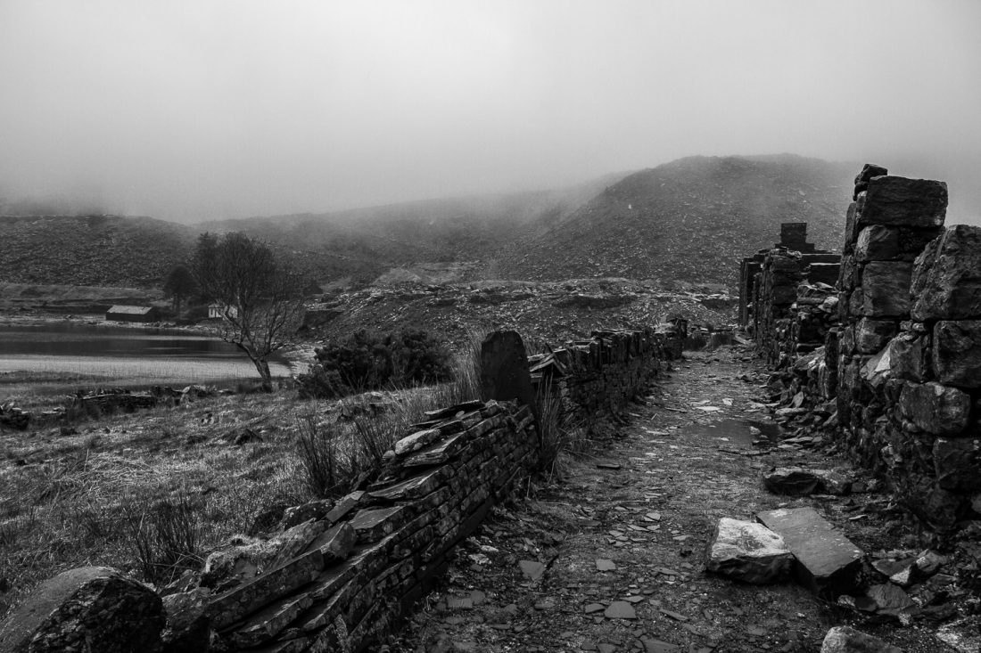 A Black And White Photograph Of The Abandoned And Ruined Buildings Of The Cwmorthin Quarry On A Misty Day In North Wales.