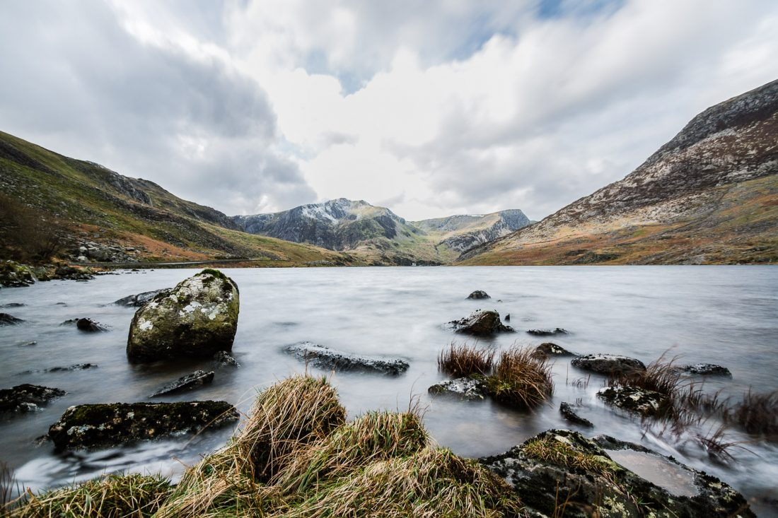 A Long Exposure Photograph Showing Llyn Ogwen With A Mountainous Background And Dynamic Sky In Snowdonia, Wales.