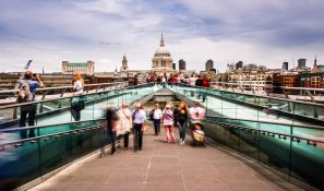 A Long Exposure Photograph Showing People Walking Over And Photographing The Millennium Bridge, London, With St Paul's Cathedral In The Background.