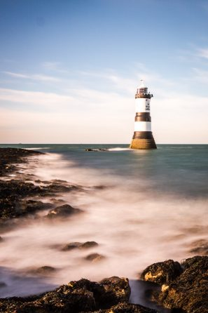 A Long Exposure Photograph Showing Trwyn Du Lighthouse And The Sea Crashing Over The Rocky Shore In Anglesey, Wales.