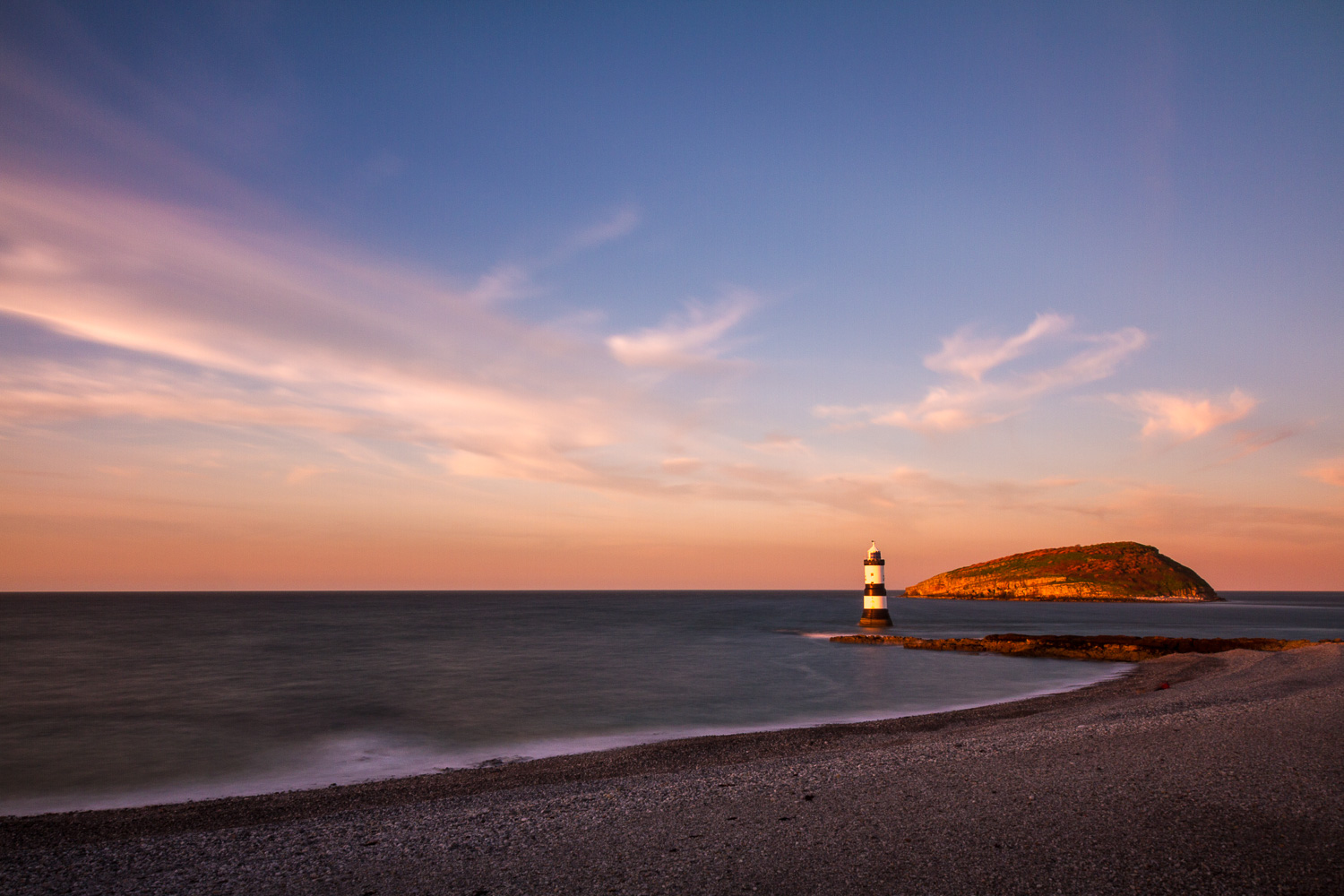 A Long Exposure Photograph Showing Trwyn Du Lighthouse And Puffin Island From The Shoreline At Sunset With Wisps Of Cloud In The Sky.