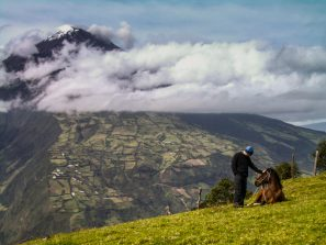 A Photograph Showing A Man Touching A Horse, Which Is Lying On The Ground, With The Volcan Tungurahua Volcano In The Background, Ecuador.