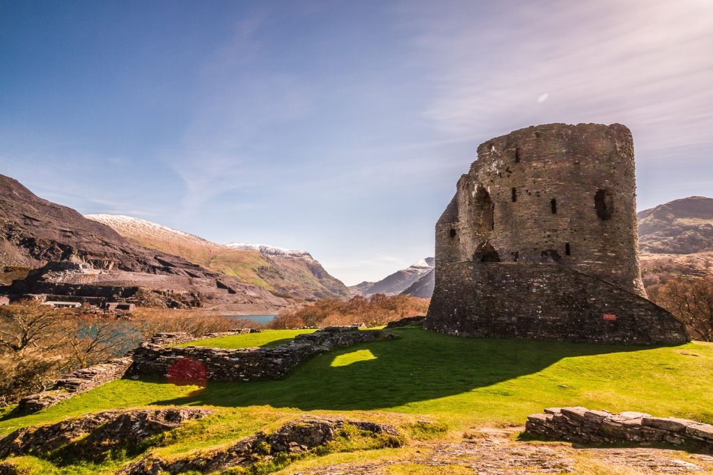 A photograph showing Castle Dolbadarn in the sun with a mountains background in the Snowdonia National Park, Wales.