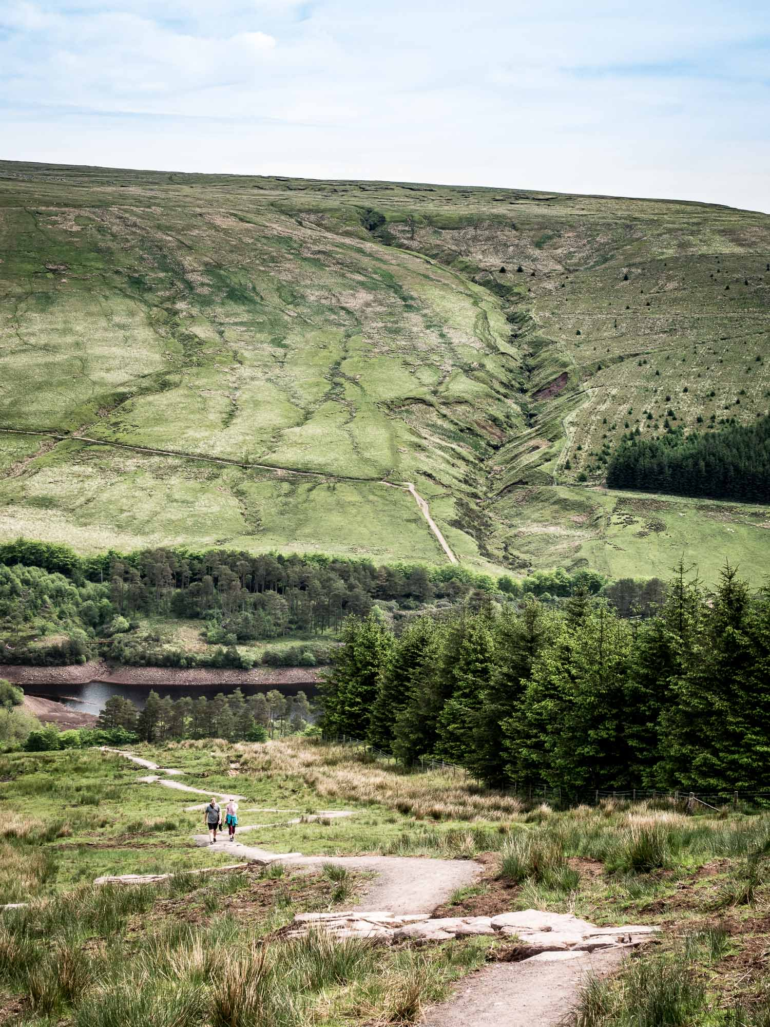 A Landscape Photograph Showing Two Hikers Beginning The Ascent Up To Graig Fan Ddu, With Neuadd Reservoir In The Background, In The Brecon Beacons National Park, Wales.