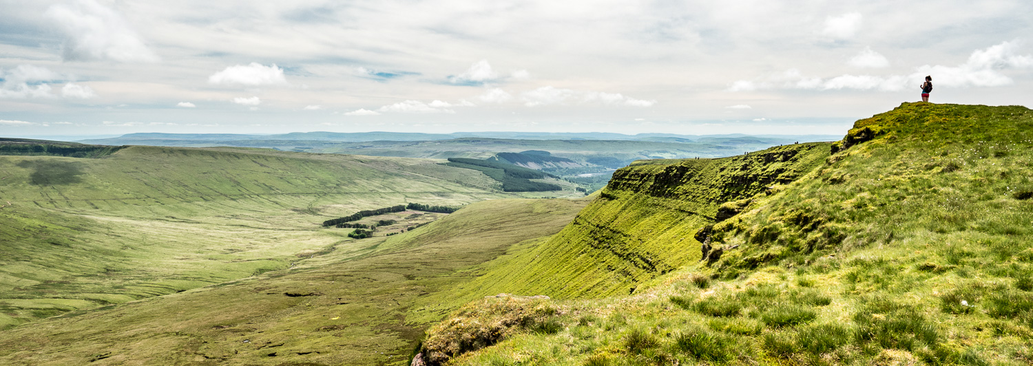 A Landscape Photograph Showing A Lone Female Hiker Looking Out From Craig Gwaun Taf Over The Neuadd Valley In The Brecon Beacons National Park, Wales.