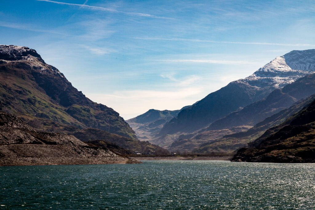 A photograph showing Llyn Peris lake with a mountainous backdrop on the edge of the Snowdonia National Park, Wales.