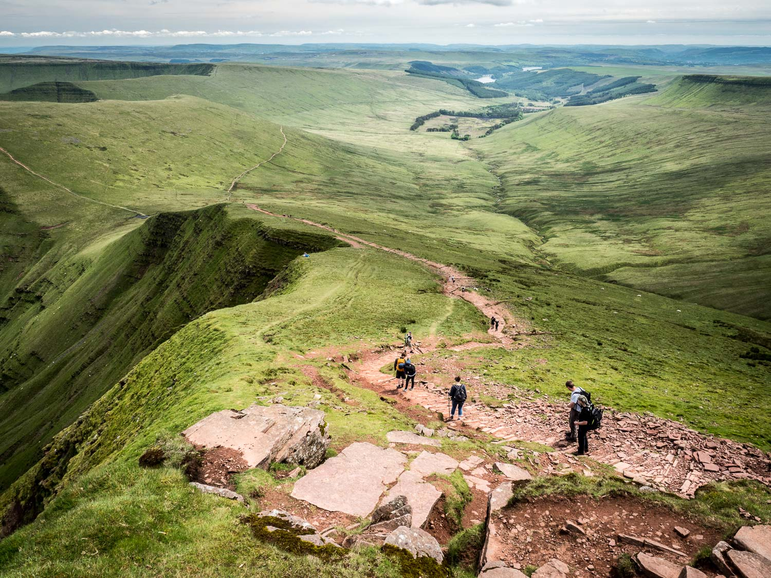 A Landscape Photograph Showing Walkers Descending From Pen Y Fan Into The Neuadd Valley In The Brecon Beacons National Park, Wales.