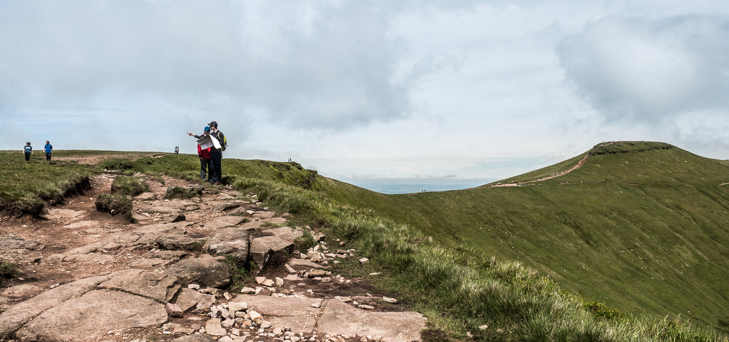 A Landscape Photograph Showing Walkers Consulting A Map On The Path To Corn Du In The Brecon Beacons National Park, Wales.