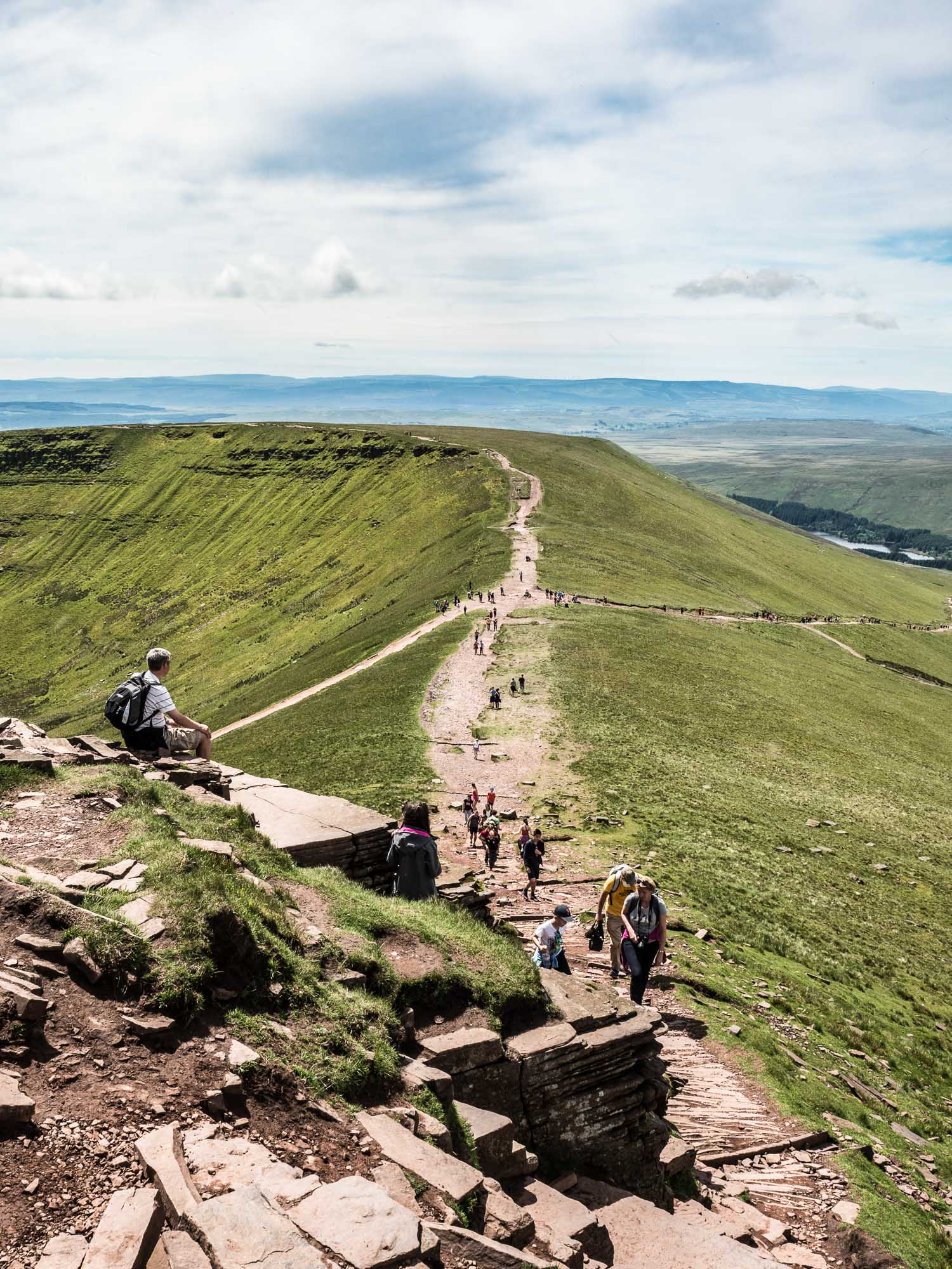 A Landscape Photograph Showing The View Down From Corn Du, With Hikers Streaming Up The Hill, In The Brecon Beacons National Park, Wales.