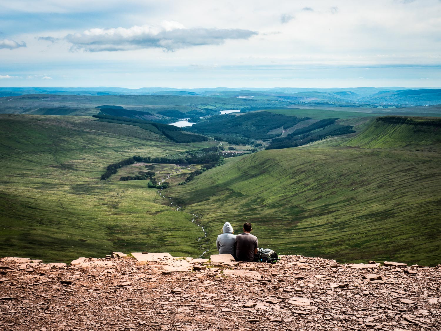 A Landscape Photograph Showing A Couple Sitting On A Ledge On Pen Y Fan Having Lunch, Looking Out At The Neuadd Valley In The Brecon Beacons National Park, Wales.