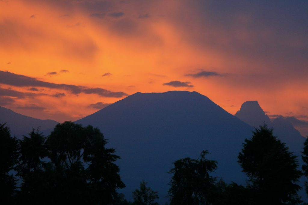 A photograph showing a red and orange sunset sky over the silhouette of Mount Bisoke volcano in the Volcanoes National Park, Virunga Mountains, Rwanda.