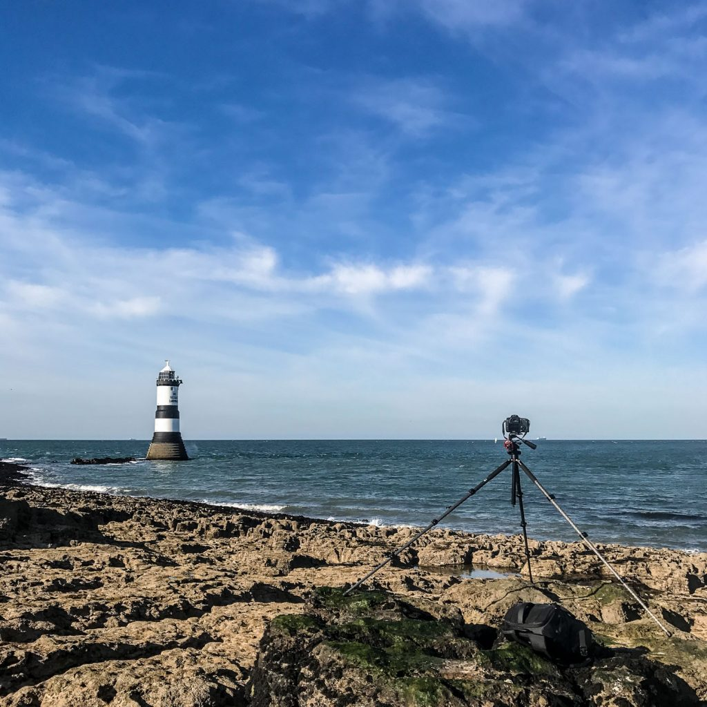 A photograph of a Canon 7D DSLR camera on a tripod balanced on rocks taking a long exposure photograph of Trwyn Du Lighthouse at Penmon Point on Anglesey, Wales.