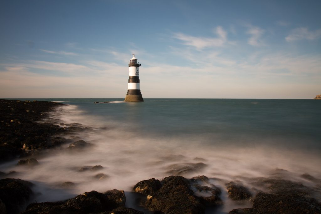A long exposure photograph of Trwyn Du Lighthouse at Penmon Point on Anglesey, Wales.