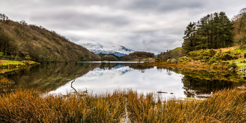 A landscape photograph showing Llyn Cynwch on the Precipice Walk in Snowdonia with the snow-covered Cadair Idris mountain in the background.