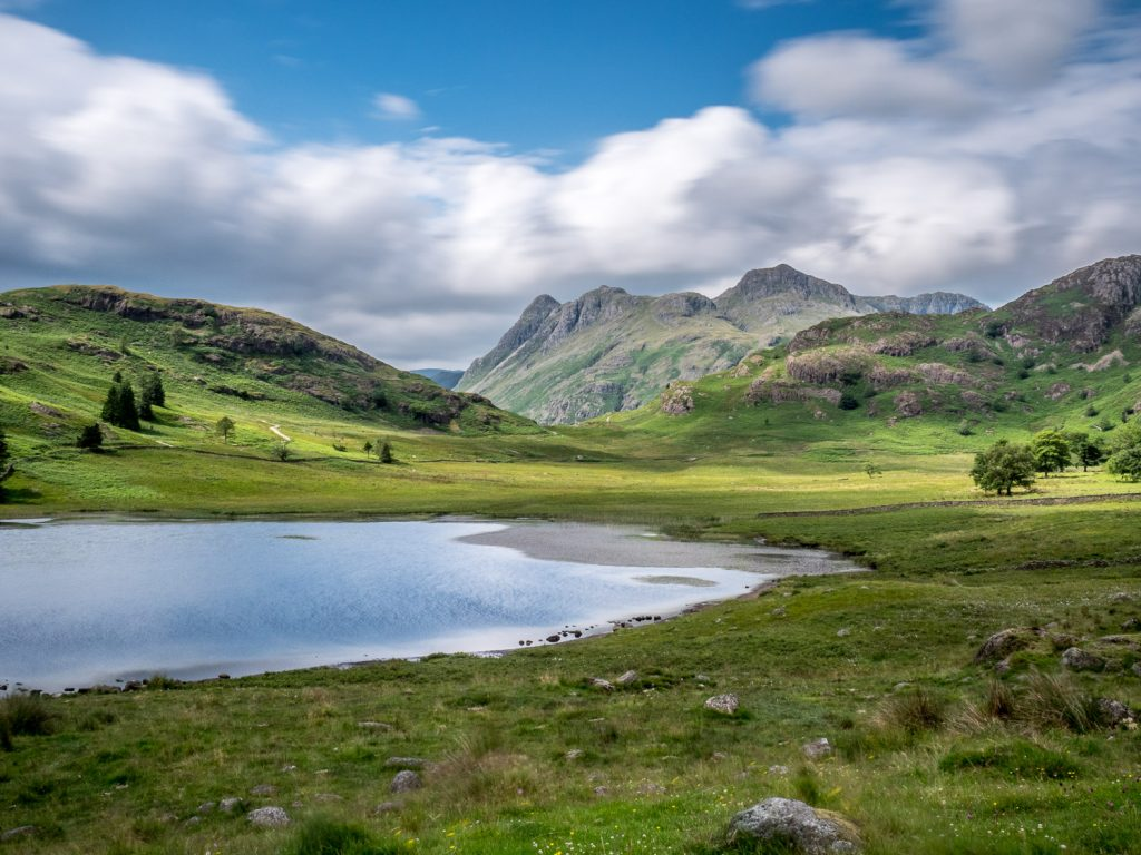 A landscape photograph showing Blea Tarn and the Langdale Pikes on a sunny day with blue skies, from my Lake District photography tour.