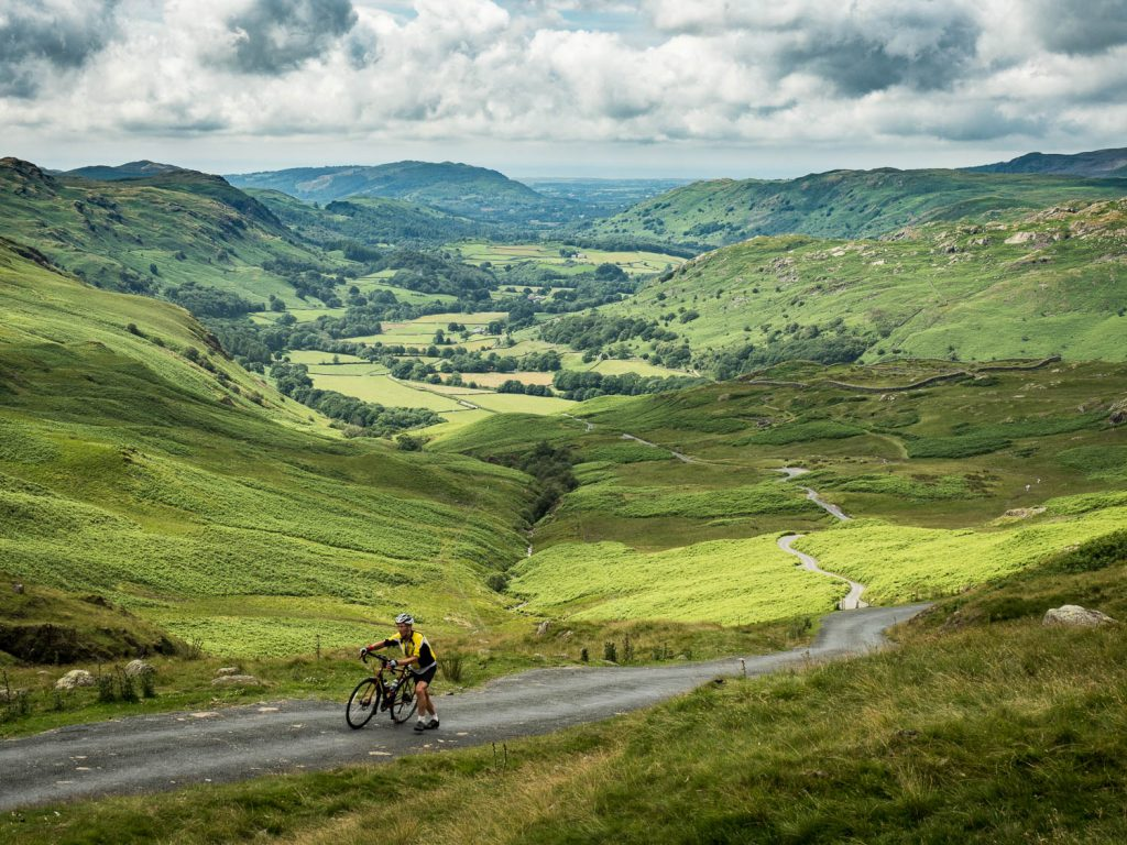 A landscape photograph of a cyclist pushing his bicycle towards the top of Hardknott Pass in the Lake District, with the valley behind, from my Lake District photography tour.