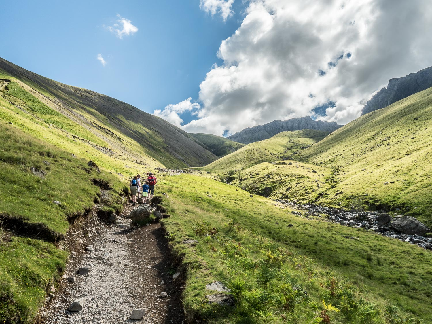 A Landscape Photograph Of A Family Walking Up The Path To Scafell Pike In The Lake District.