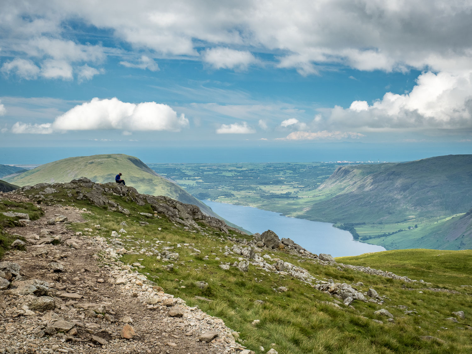 A Landscape Photograph Showing A Lone Hiker Resting On A Rock On The Scafell Pike Hollow Stones Route, With Wast Water In The Background In The Lake District.