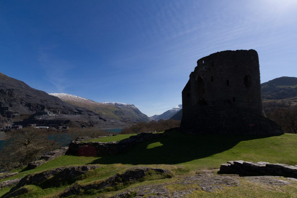 A low exposure photograph of Dolbadarn Castle in Snowdonia, showing detail in the sky and bright areas, but black shadows with no detail.