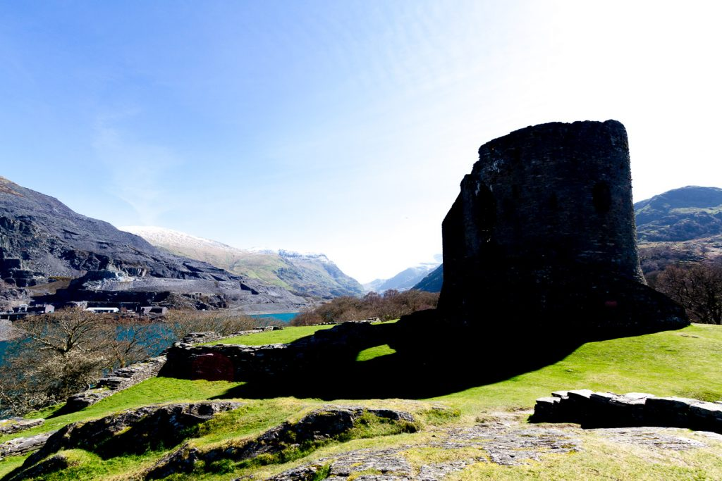 A photograph of Dolbadarn Castle in Snowdonia, showing very dark shadows contrasting with very bright sky.
