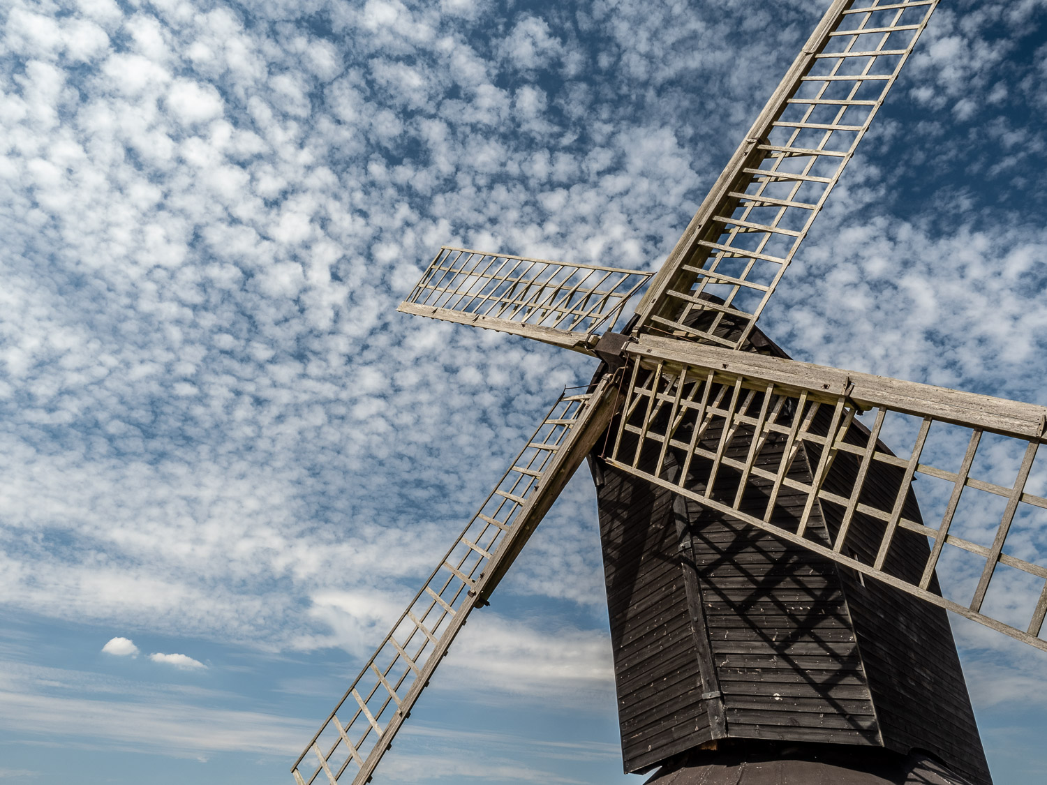 A Photograph Looking Up At Pitstone Windmill In Front Of A Blue Sky With Lots Of Small, White Clouds.