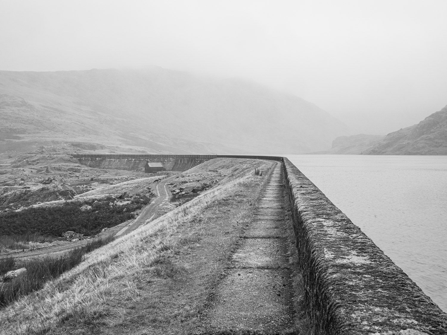 A Black And White Landscape Photograph Of Seathwaite Tarn Reservoir On A Misty Day In The Lake District